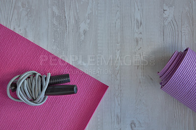 Buy stock photo High angle shot of exercise mats and a skipping rope on a wooden surface