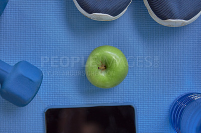 Buy stock photo High angle shot of everyday workout essentials placed around an apple against a blue background