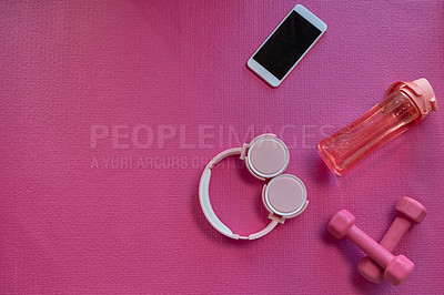 Buy stock photo High angle shot of a cellphone, water bottle, headphones and a pair of dumbbells against a pink background