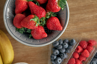 Buy stock photo High angle shot of strawberries, raspberries and blueberries on a counter top in an empty kitchen