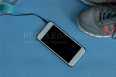 Buy stock photo High angle shot of a cellphone and sneakers laid out on a blue exercise mat after a workout