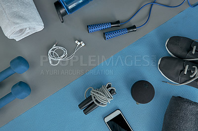 Buy stock photo High angle shot of a variety of workout equipment laid out on a blue exercise mat before a workout