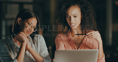 Buy stock photo Cropped shot of two attractive businesswomen sitting together and looking confused while using a laptop in the office at night