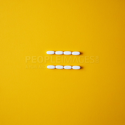 Buy stock photo Studio shot of  tablets arranged in the shape of an equals sign against a mustard background