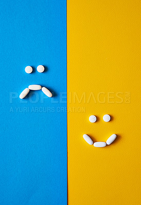 Buy stock photo Studio shot of tablets arranged in the shapes of a sad face and a smiley face against a mixed background