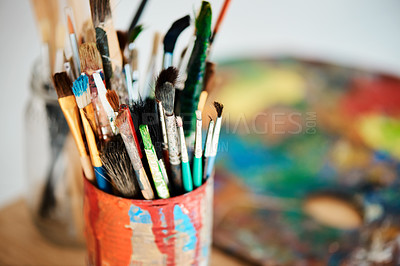 Buy stock photo Cropped shot of a tin full of paintbrushes in an empty art studio after a painting class