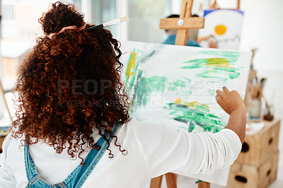 Buy stock photo Cropped shot of an unrecognizable artist sitting and painting on a canvas during a painting session in an art studio