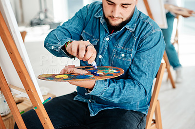 Buy stock photo Cropped shot of a handsome young artist squeezing paint onto a palette during an art class in the studio
