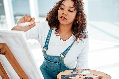 Buy stock photo Cropped shot of an attractive young artist sitting alone and painting during an art class in the studio