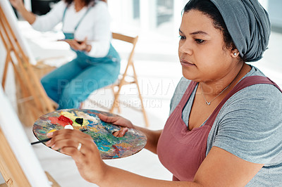 Buy stock photo Cropped shot of an attractive young woman sitting with her friends and painting during an art class in the studio