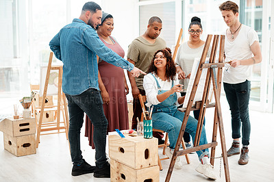 Buy stock photo Full length shot of an attractive young woman sitting and explaining her artwork to her friends during an art class
