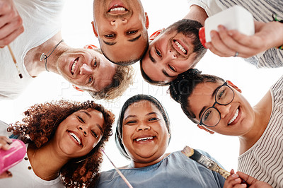 Buy stock photo Low angle portrait of a diverse group of friends huddled together during an art class in the studio
