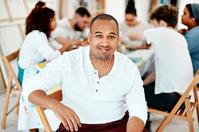 Buy stock photo Cropped portrait of a handsome young man sitting with his friends during an art class in the studio