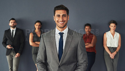 Buy stock photo Portrait of a handsome young businessman posing in studio with his colleagues standing in the background