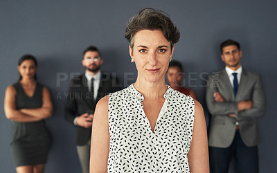 Buy stock photo Portrait of an attractive young businesswoman posing in studio with her colleagues standing in the background