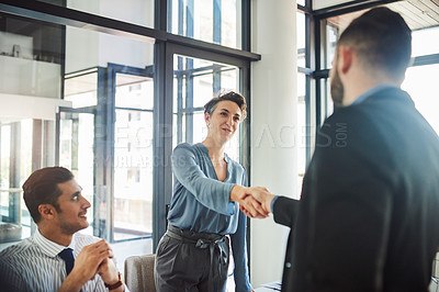 Buy stock photo Cropped shot of two businesspeople shaking hands while attending a meeting in the boardroom