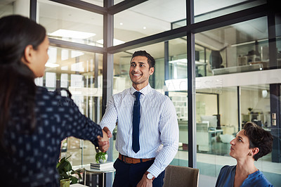 Buy stock photo Shot of two people shaking hands while attending a meeting in a boardroom