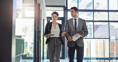 Buy stock photo Shot of two businesspeople having a conversation while walking through the office