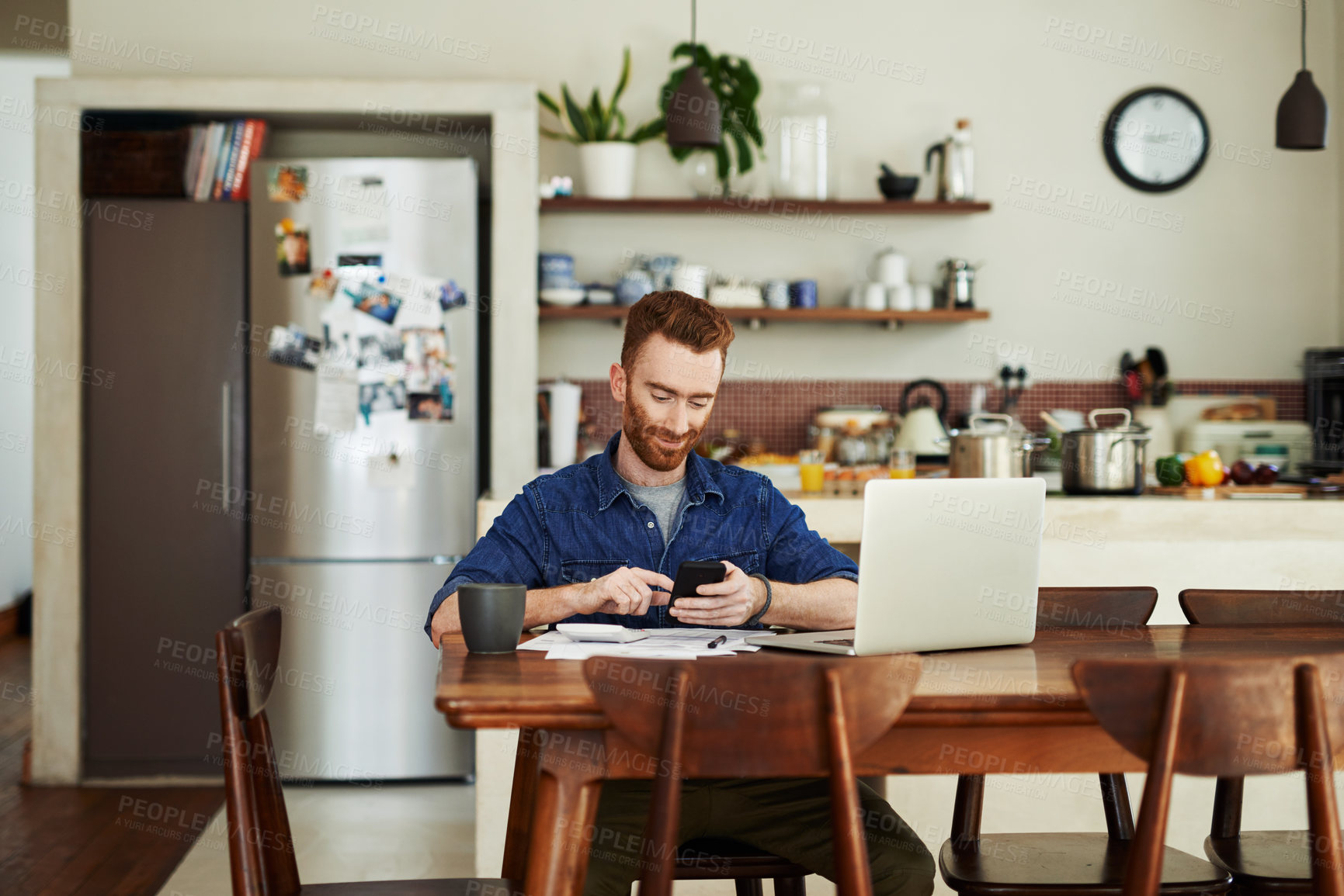 Buy stock photo Shot of a young man using a cellphone while going through paperwork at home
