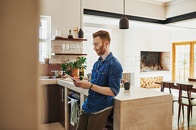 Buy stock photo Shot of a young man using a digital tablet in the kitchen at home