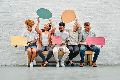 Buy stock photo Full length shot of a diverse group of businesspeople sitting together and holding speech bubbles in the office