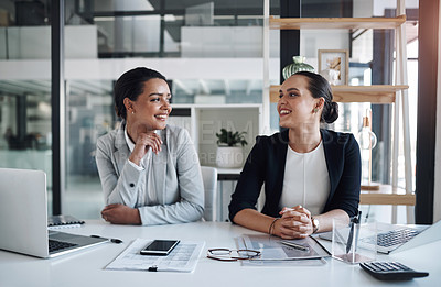 Buy stock photo Cropped shot of two attractive young businesswomen working together inside a modern office