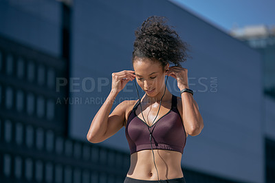 Buy stock photo Shot of a sporty young woman listening to music while exercising in the city