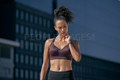 Buy stock photo Shot of a sporty young woman taking her pulse while exercising in the city