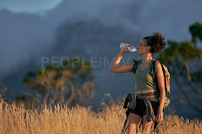 Buy stock photo Shot of an attractive young woman drinking water while hiking out in the mountains on a sunny day