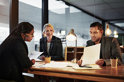 Buy stock photo Shot of a group of businesspeople having a late night meeting in a modern office