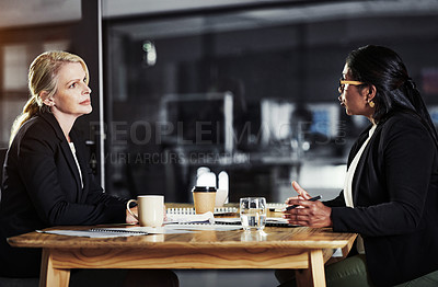 Buy stock photo Shot of two businesswomen having a late night meeting in a modern office