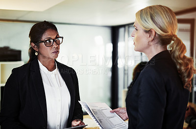 Buy stock photo Shot of two businesswomen having a late night discussion in a modern office