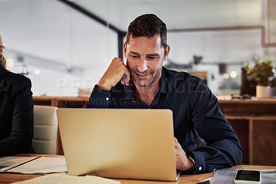 Buy stock photo Shot of a mature businessman using a laptop during a late night in a modern office