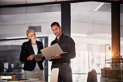 Buy stock photo Shot of a businessman and businesswoman using wireless devices during a late night discussion in a modern office