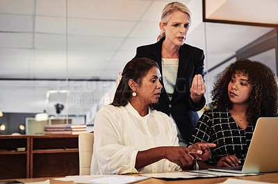 Buy stock photo Shot of a group of businesspeople using a laptop during a late night in a modern office