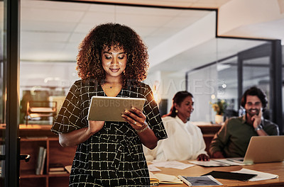 Buy stock photo Shot of young businesswoman using a digital tablet during a late night meeting in a modern office