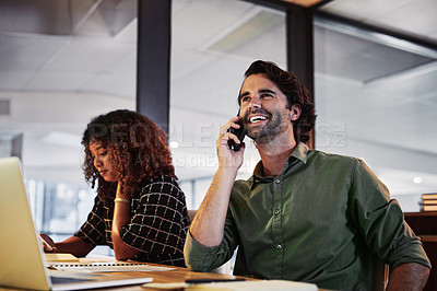 Buy stock photo Shot of a young businessman using a smartphone during a late night in a modern office