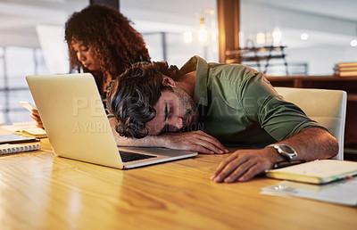 Buy stock photo Shot of a young businessman sleeping at his desk during a late night in a modern office
