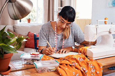 Buy stock photo Shot of a beautiful young woman making notes while working on a garment at home