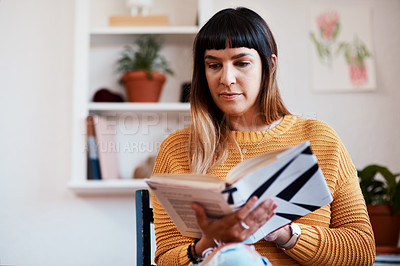 Buy stock photo Cropped shot of a beautiful young woman reading a book while relaxing at home