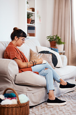 Buy stock photo Shot of an attractive young woman drawing while relaxing on the sofa at home