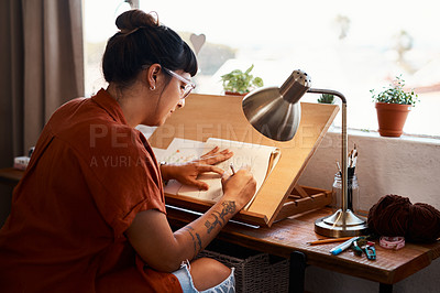 Buy stock photo Cropped shot of a young woman sketching at home