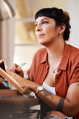 Buy stock photo Shot of a young woman looking thoughtful while sketching at home