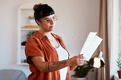 Buy stock photo Cropped shot of a young woman looking at paperwork at home