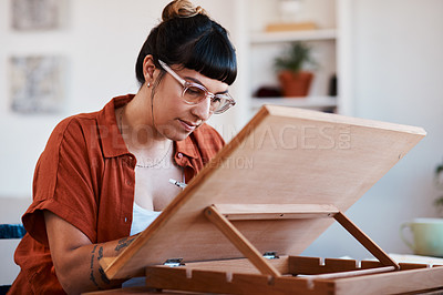 Buy stock photo Shot of an artist sketching in a desk easel at home