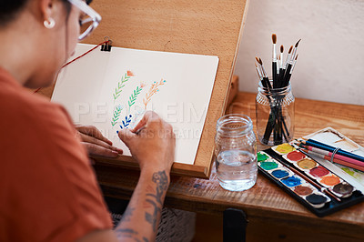 Buy stock photo Cropped shot of an unrecognizable woman working on a painting at home