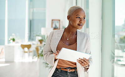 Buy stock photo Shot of a young businesswoman using a digital tablet while looking out the window in an office