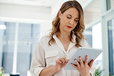 Buy stock photo Cropped shot of an attractive young businesswoman using a digital tablet inside her office