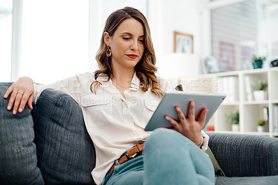 Buy stock photo Cropped shot of an attractive young businesswoman using a digital tablet while sitting on a sofa inside her office