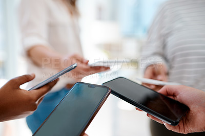 Buy stock photo Cropped shot of an unrecognizable group of businesswomen using their smartphones inside an office